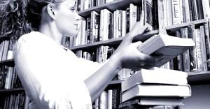 Female librarian putting books on shelves